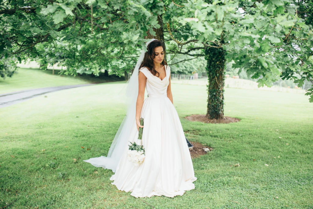 The bride stands in the middle pf a green lawn with two tall trees behind her. She is wearing a white satin dress and is holding a bouquet of white flowers in her right hand