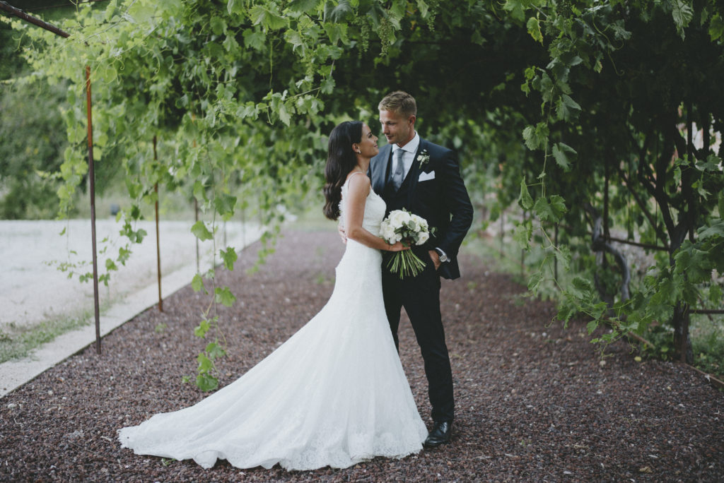 Irish bride and groom stare at each other in an embrace, the bride is holding a bouquet of white roses. The background is comprised of an arch of draping ivy and a gravel path