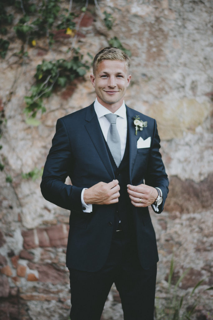 Blonde Irish groom stands smiling to the camera holding the lapels of his dark navy suit
