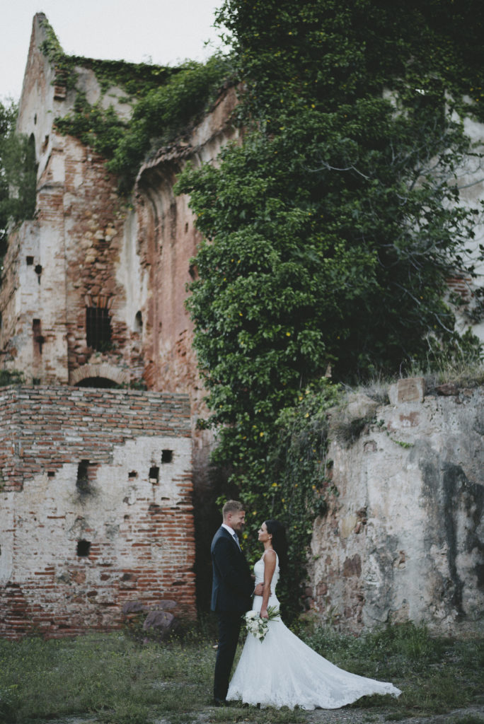 Irish bride and groom stand profile to the camera in front of castle ruins draped in ivy and moss. The bride and groom are small in the image and take up about 1/3rd of the image