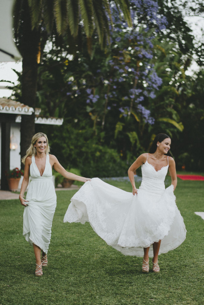 Irish bride sans veil is walking across a green lawn, her white dress is being held by both her and a bridesmaid also wearing a white dress who is holding up her own dress