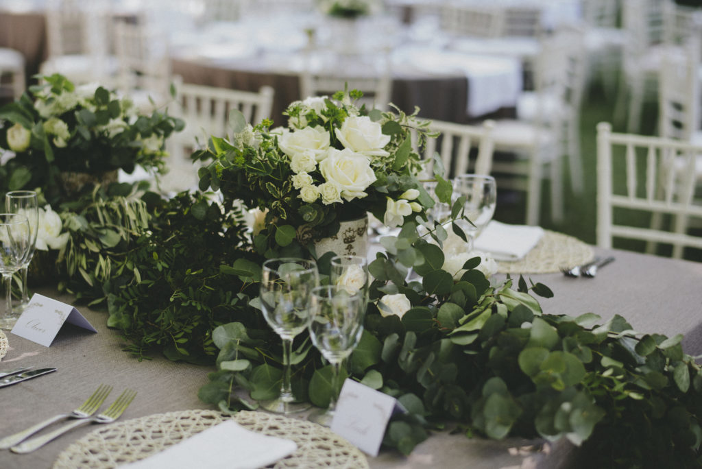Table centerpiece comprised of white roses and a large display of greenery. Table settings of three wine glasses are also set in front of a crochet table mat and silver cutlery per guest