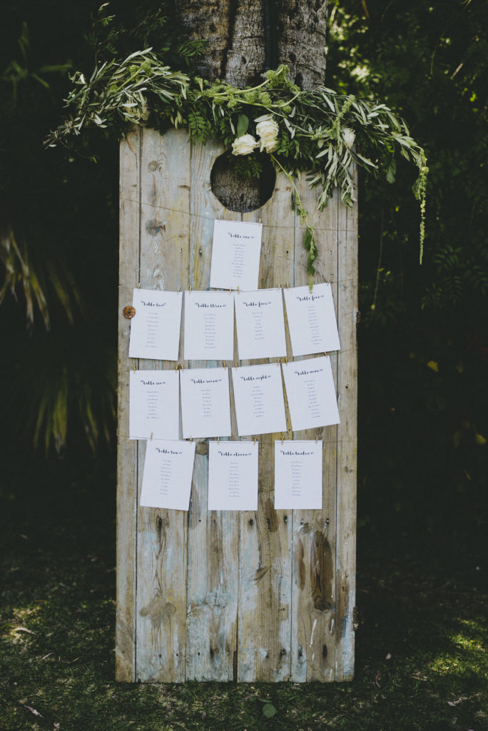 Distressed wood board used to display table seating plan on white card with cursive text. A large bundle of greenery is places on the top and drapes onto the wood board partially