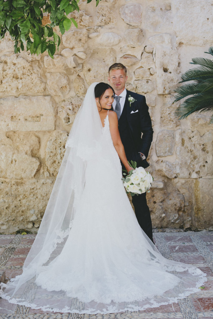 Irish bride and groom stand against each-other looking into camera with bride in front facing groom. White veil is spread out across the ground and covers the back of her dress.