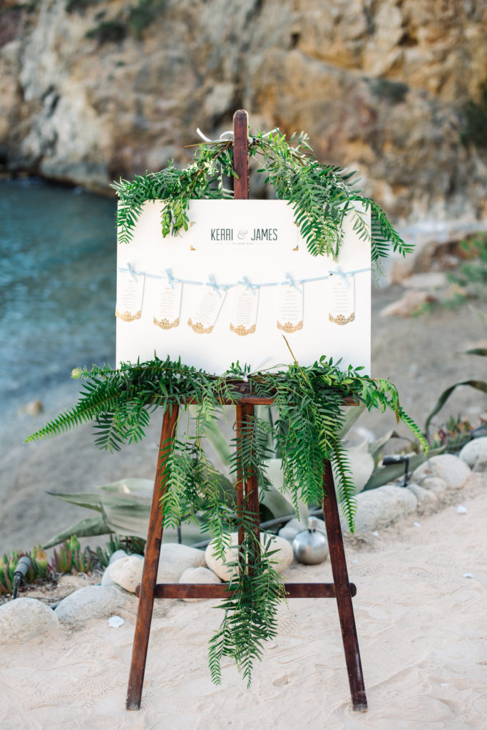 A piece of white card on a dark brown wooden easel, across the card are six smaller cards displaying the seating plan attached with a light blue ribbon. Green ferns decorate the top and bottom of the card and easel
