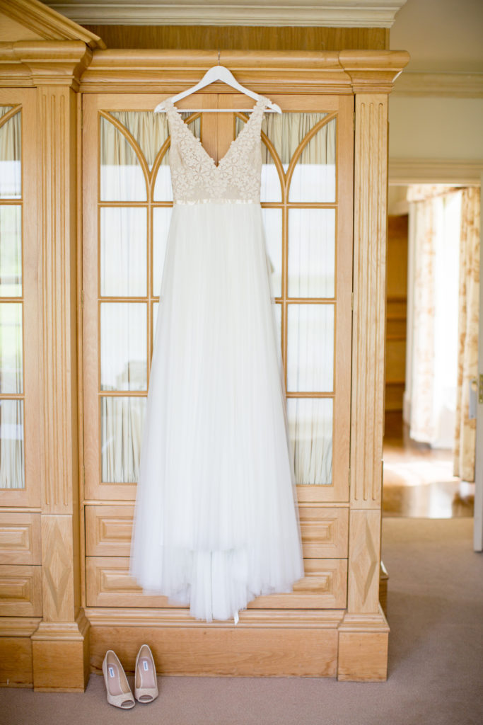 White wedding dress with lace bodice hung up against a light brown glass door wardrobe. A pair of white heeled pumps sit on the floor to the left of the dress