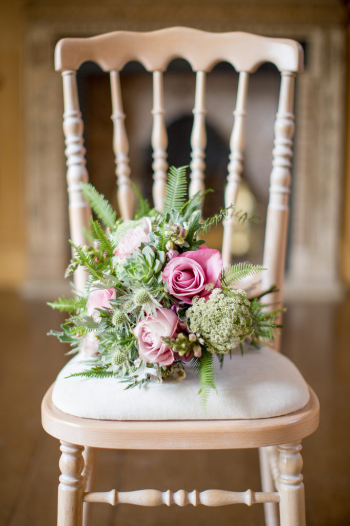A bouquet comprised of mostly assorted greenery and four large pink roses sits on the seat of a light brown wooden chair with a white cushion