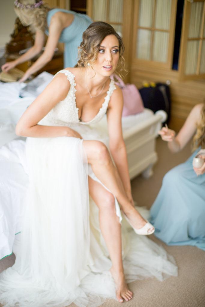 Irish bride sitting on a bed in white V-neck wedding dress putting one a white high heel
