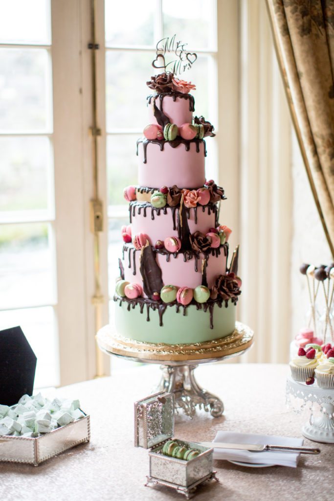 A five tiered cake with a mint green base layer and 4 pastel pink layers on top. The cake has chocolate dripping down the sides and is decorated with macaroons and flowers. On the top of the cake is a silver topper that says Mr and Mrs