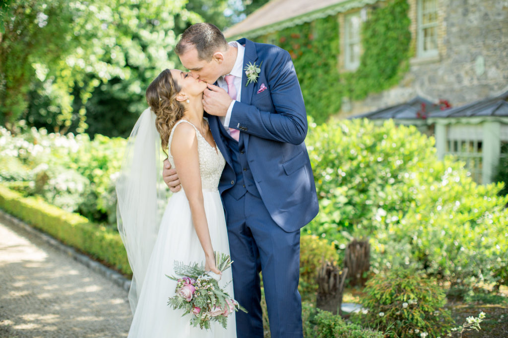 Irish bride and groom stand portrait to the camera in a green garden kissing. The bride is holding a pink and green bouquet in her right hand