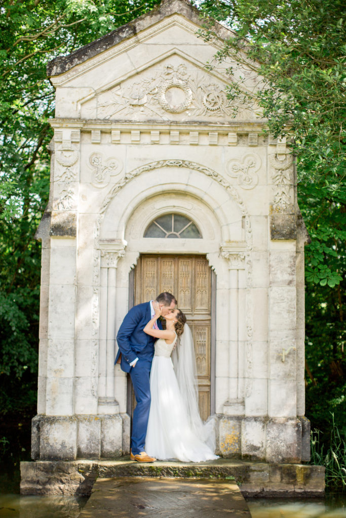 Irish bride and groom stand kissing against a large pale grey stone door in the middle of a large group of trees