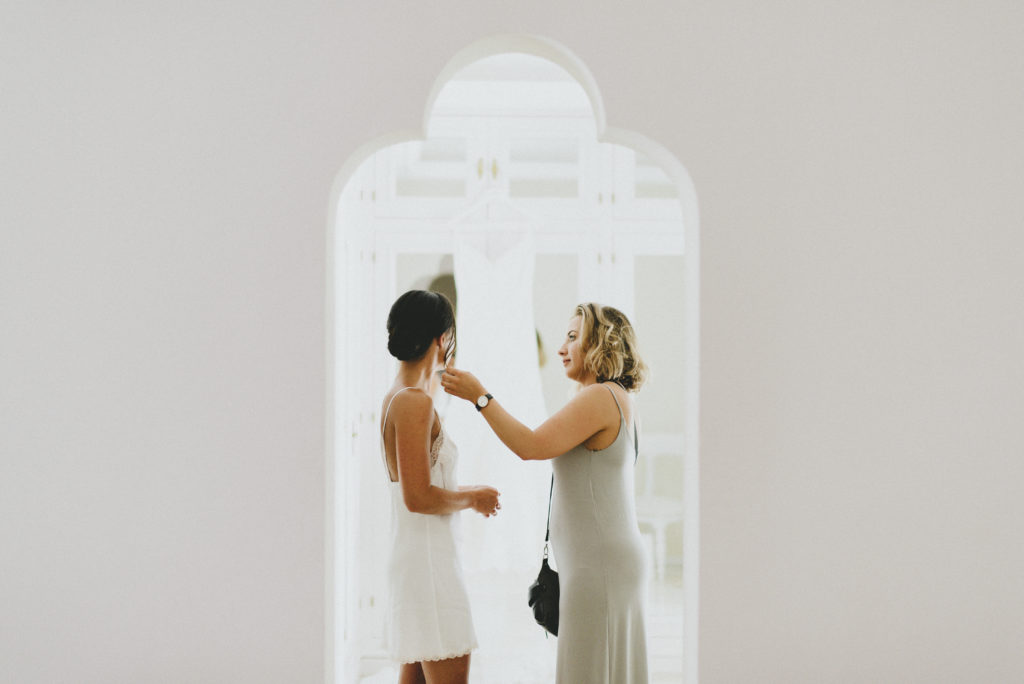 Dark haired Irish woman stands in grey arch in white camisole getting ready for her wedding day