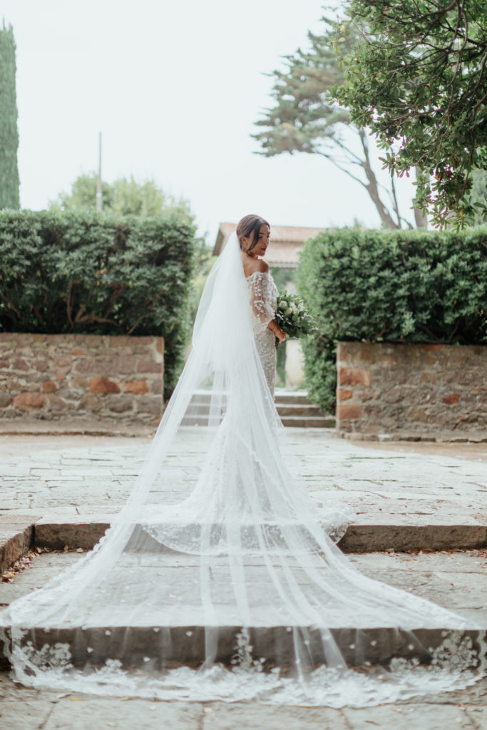 Irish bride stands at the top of two cobble steps, her long white veil draped behind her spilling off the steps. She is looking over her shoulder at the camera