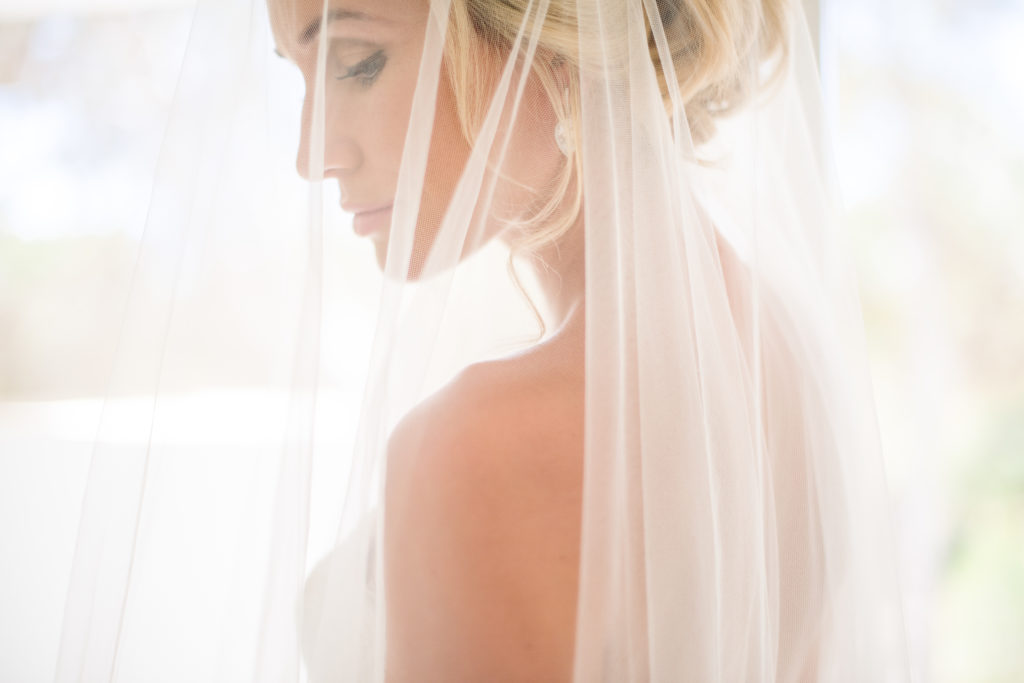 A blonde bride is standing profile to the camera. She has a white veil draped over her face and the image is very brightly lit so it has the effect of glowing