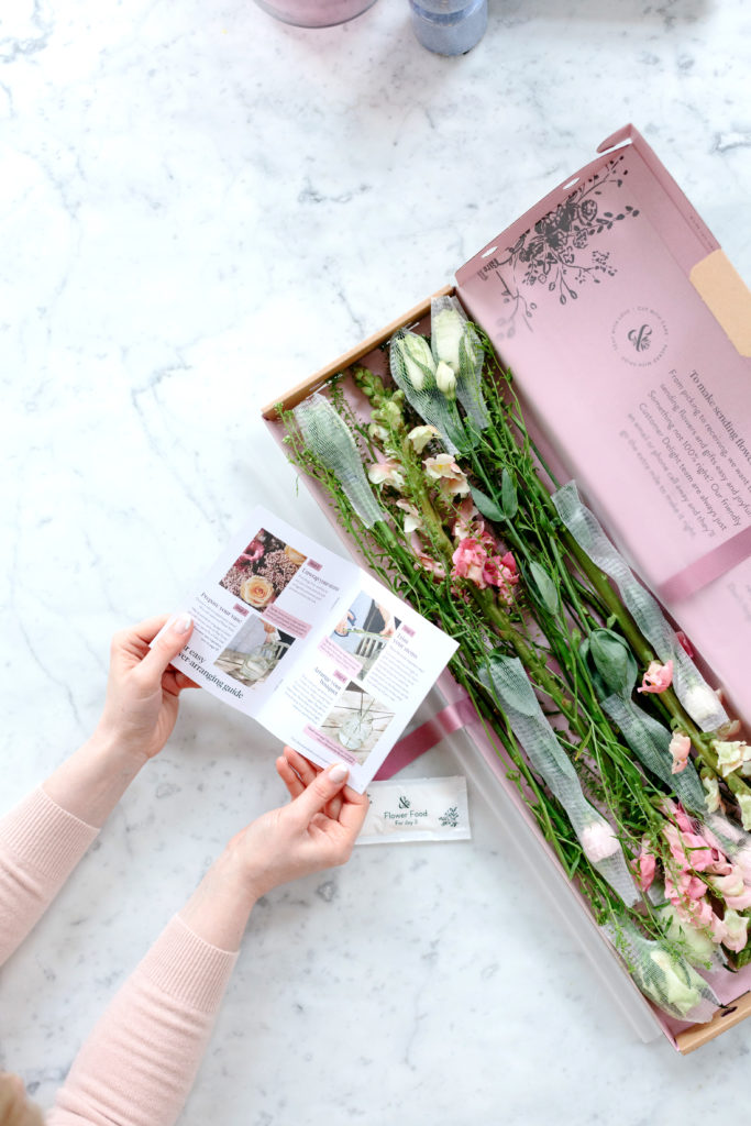 A floral wedding subscription box from Bloom and Wild. The pink box is sat on a marble table with the pink flowers inside visible. You can see a pair of women's hands to the left of the picture holding the accompanying brochure.