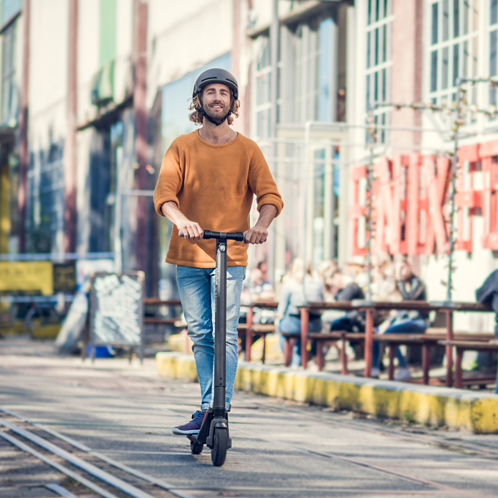 Wedding gift list option from The Wedding Shop. A ES2 Kick Scooter worth €575. Photo depicts man scooting down a road wearing jeans and a mustard jumper.