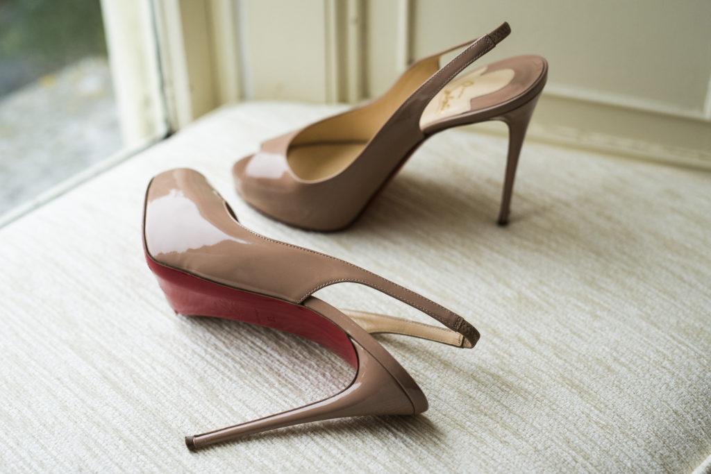 Nude Christian Louboutin slingback heels resting on a creme window cushion