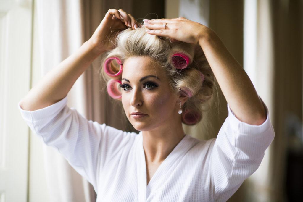 Irish bride in white robe puts pink curlers in her blonde hair