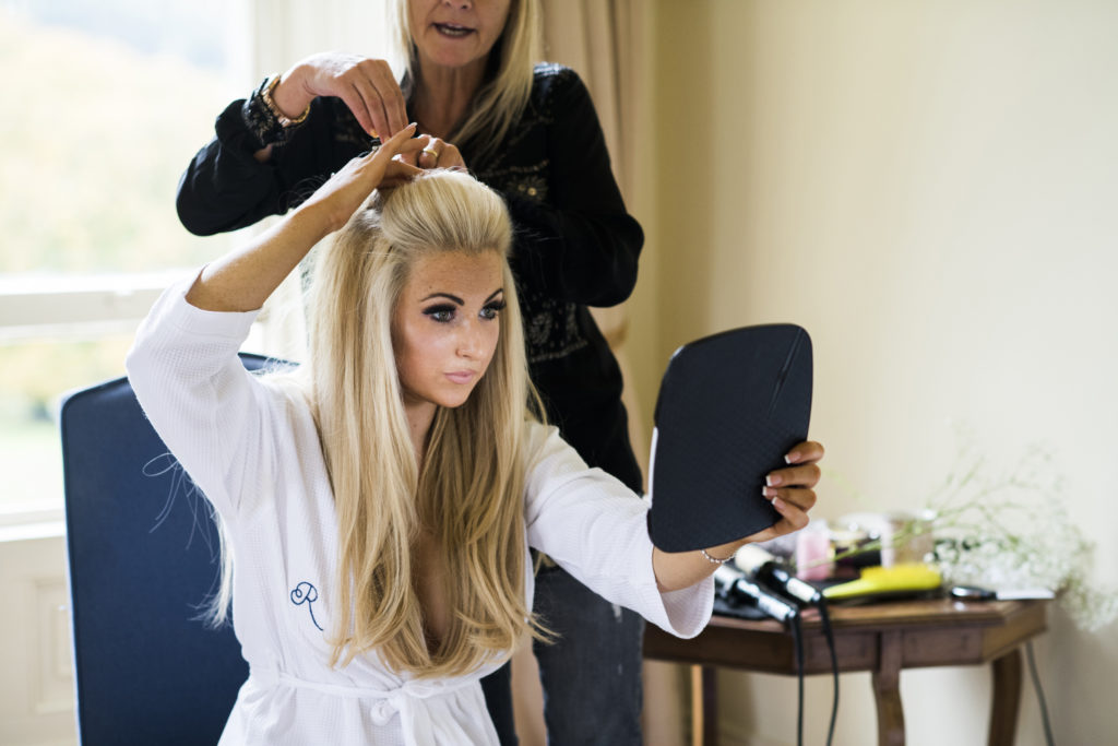 Irish bride in white robe finishing her hairstyle with the help of a blonde woman