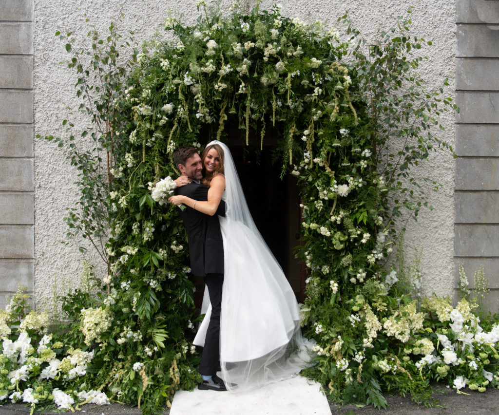 Irish bride, Joeanna Caffrey, and groom embrace outside the doors of a church. The groom is holding the bride in the air in a tight hug. Behind them is a large arch of white flowers and greenery bordering the door and grey stone wall of the church