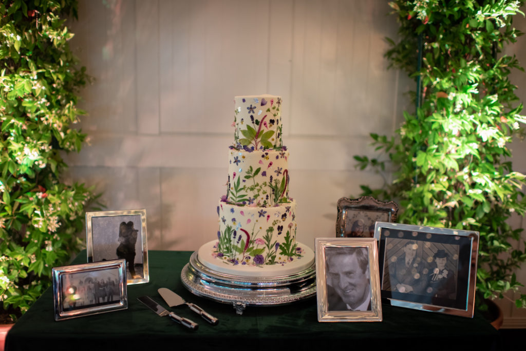 A three tiered, white buttercream wedding cake covered in small flowers and leaves in a way that gives the effect of a small garden