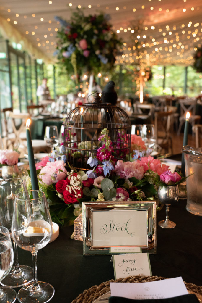 Portrait image of a table setting. Pink, blue, red and green Irish flowers surround the base of a small black birdcage with a small fake black bird perched on top. There is a silver frame in front of the centerpiece that says the word stock in calligraphy