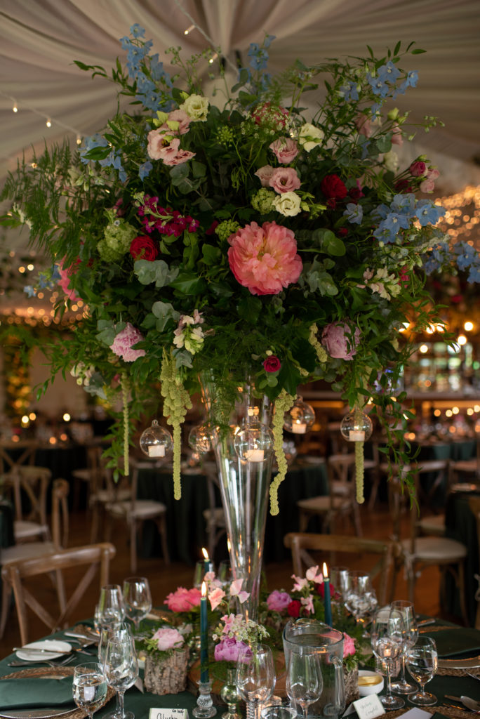 Large display of pink, white, blue and green flowers amongst a large display of green leaves and ferns on the top of a tall vase. Small glass baubles with tealights inside dangle from the greenery