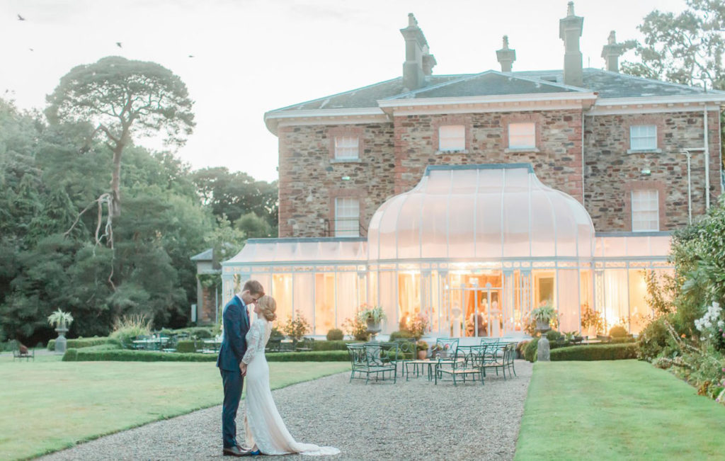 Bride and groom on lawn outside Marlfield House in Wexford. The glass conservatory is lit up in the background. The photo has a romantic feel. By In Love Photography