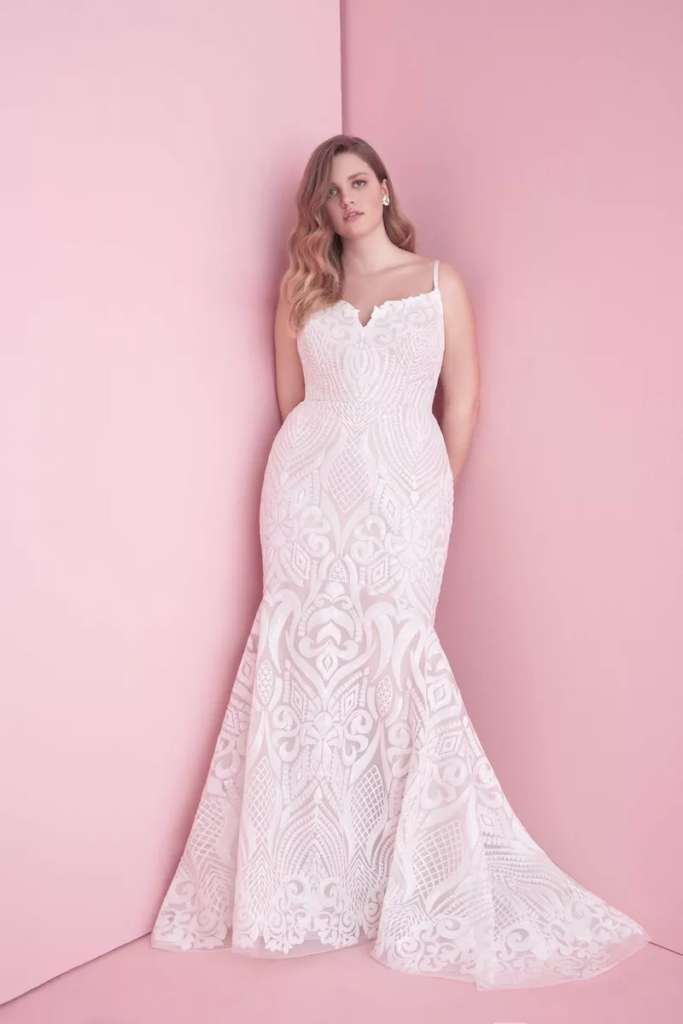 Plus-size bride in a floor length, fit and flare, white dress with a small plunge in the center of the neckline and thin straps