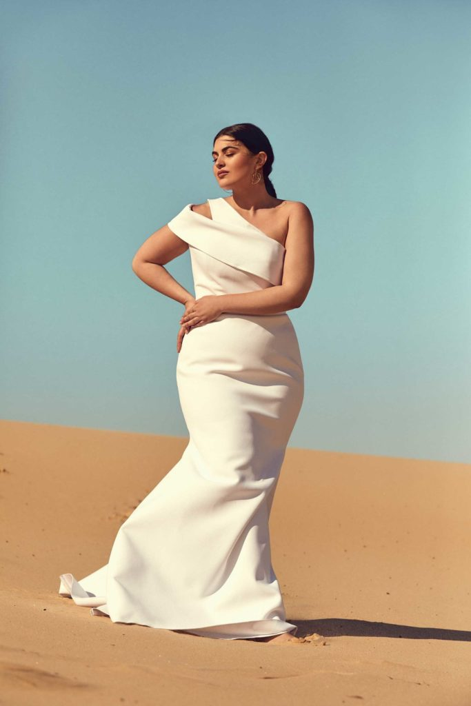 Plus-size bride in a floor length, fitted, asymmetrical white dress with two thick straps on the right shoulder
