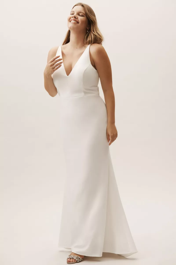 Curvy bride in a floor length, fitted white dress with plunging neckline and tapering shoulder straps