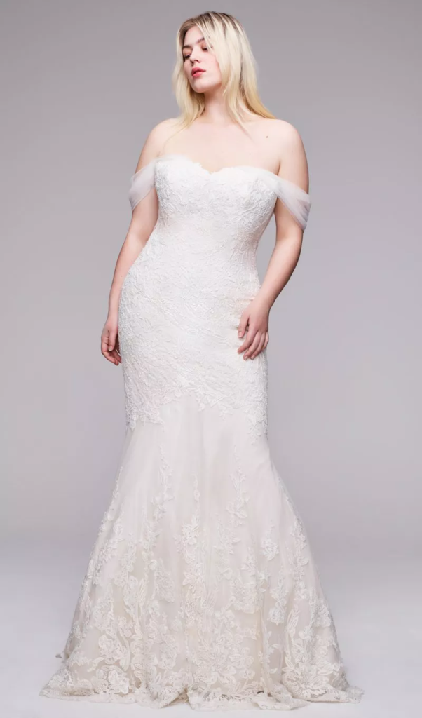 Plus size bride in a floor length, tight fitted white dress with boat neck shoulder straps, sweetheart neckline and tapering bottom