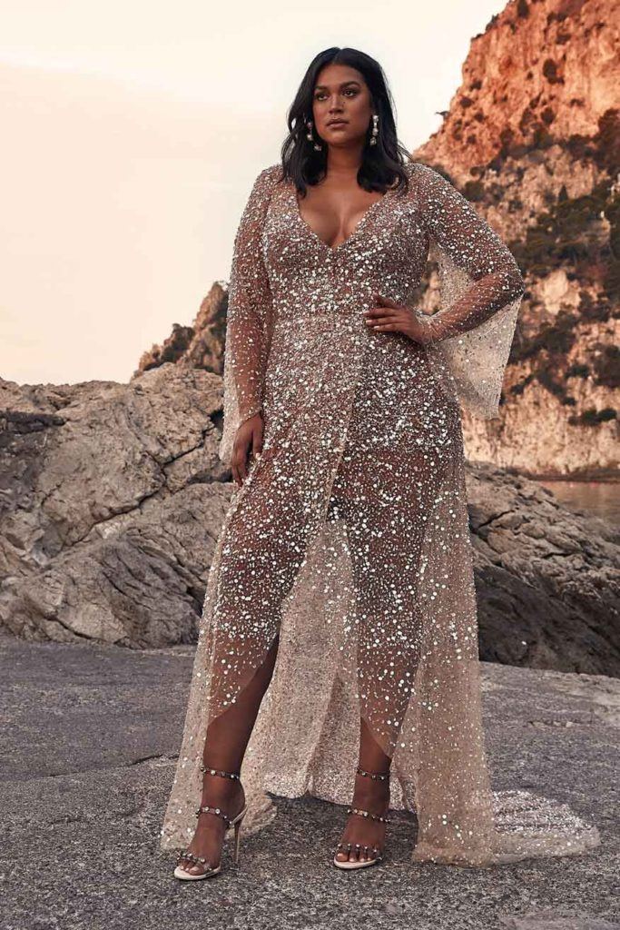 Curvy bride in floor length, silver and cold embellished wrap dress with deep V neckline, a high-low hemline and trumpet sleeves