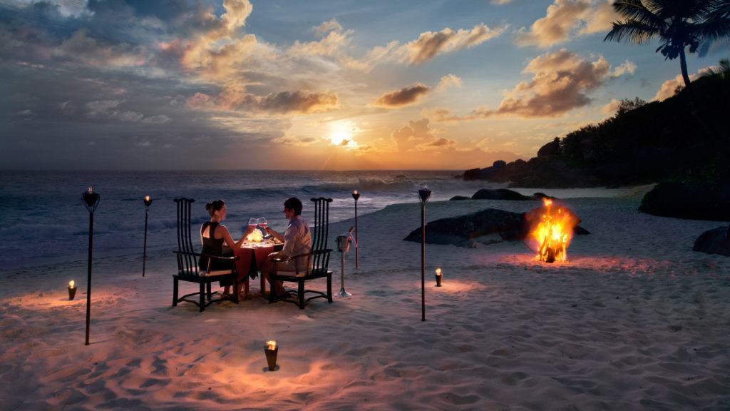 A couple having a candle lit dinner on a private beach in Kenya surrounded by torches with a bonfire burning in the background