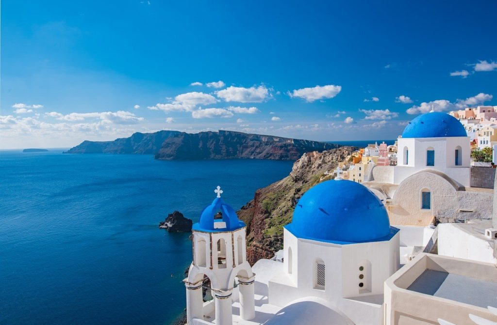 A view of the Santorini coast with an ornate white and blue building in the foreground and a mountain range in the background