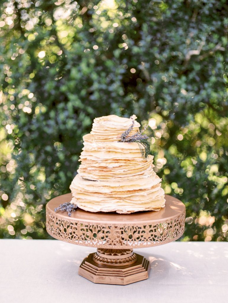 A three tier stack of pancakes held together with icing and presented on a bronze cake stand with fresh lavender decorations