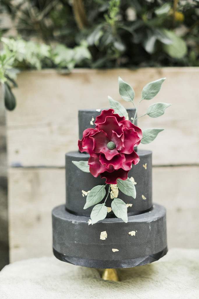 Black fondant, three tier wedding cake with large red fondant flower, fondant greenery and gold leaf decorating the front of the cake