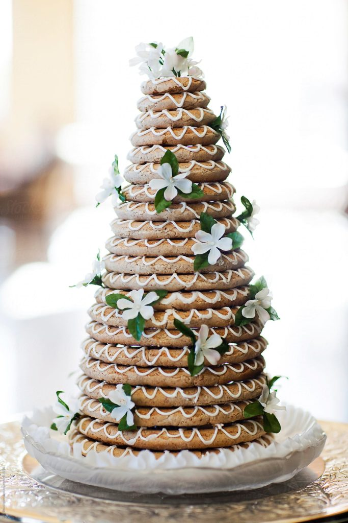 21 layers of Kransekake piled into a pyramid and decorated with white icing and white flowers