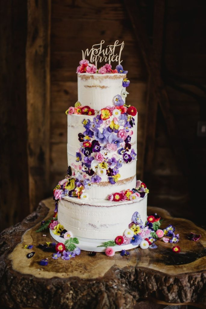 """Three tier wedding cake decorated with rustic style white buttercream icing, a """"Just Married"""" cake topper and adorned with purple, pink, yellow and white edible flowers across all three layers"""
