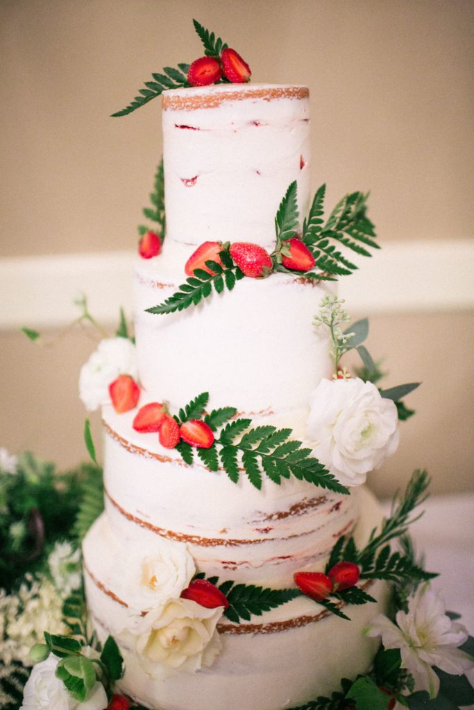 Four tier wedding cake decorated with rustic style white buttercream icing, ferns, white roses and sliced strawberry