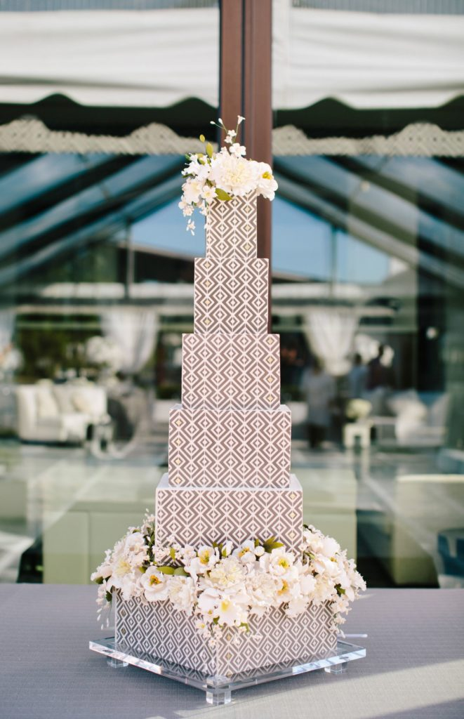 A six tier grey and white geometric designed wedding cake adorned with while flowers on the top layer and the base layer