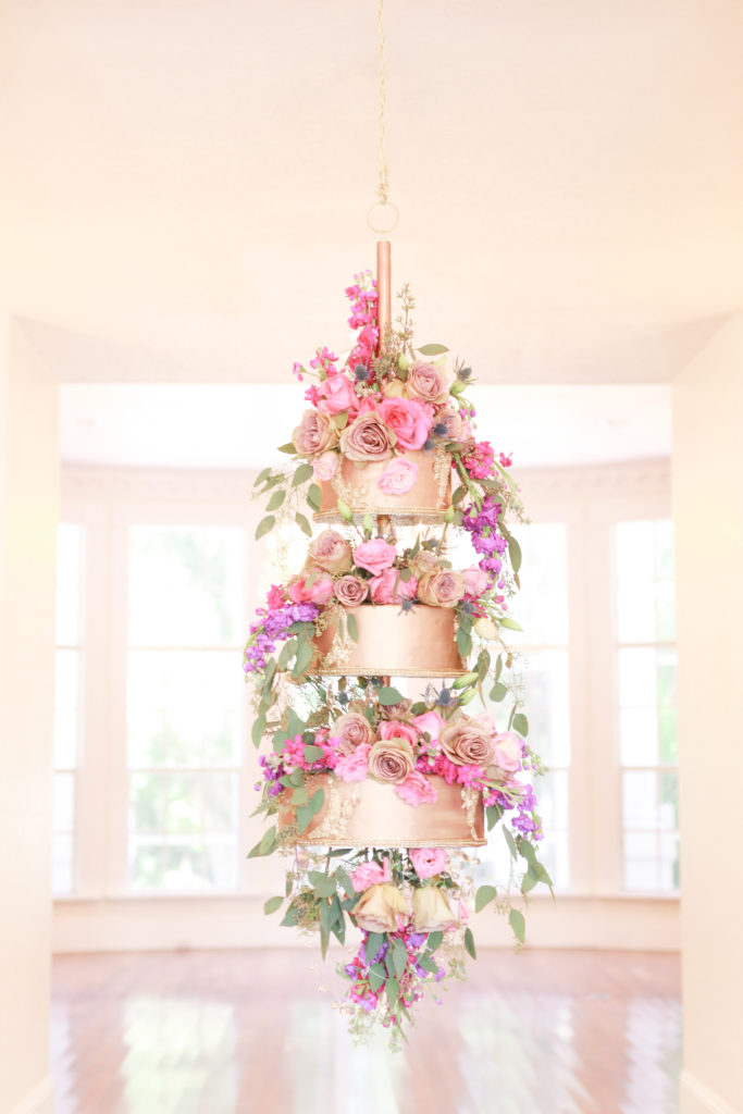 Three tiered gold wedding cake hanging from the ceiling covered in pink, purple and white roses with draping greenery