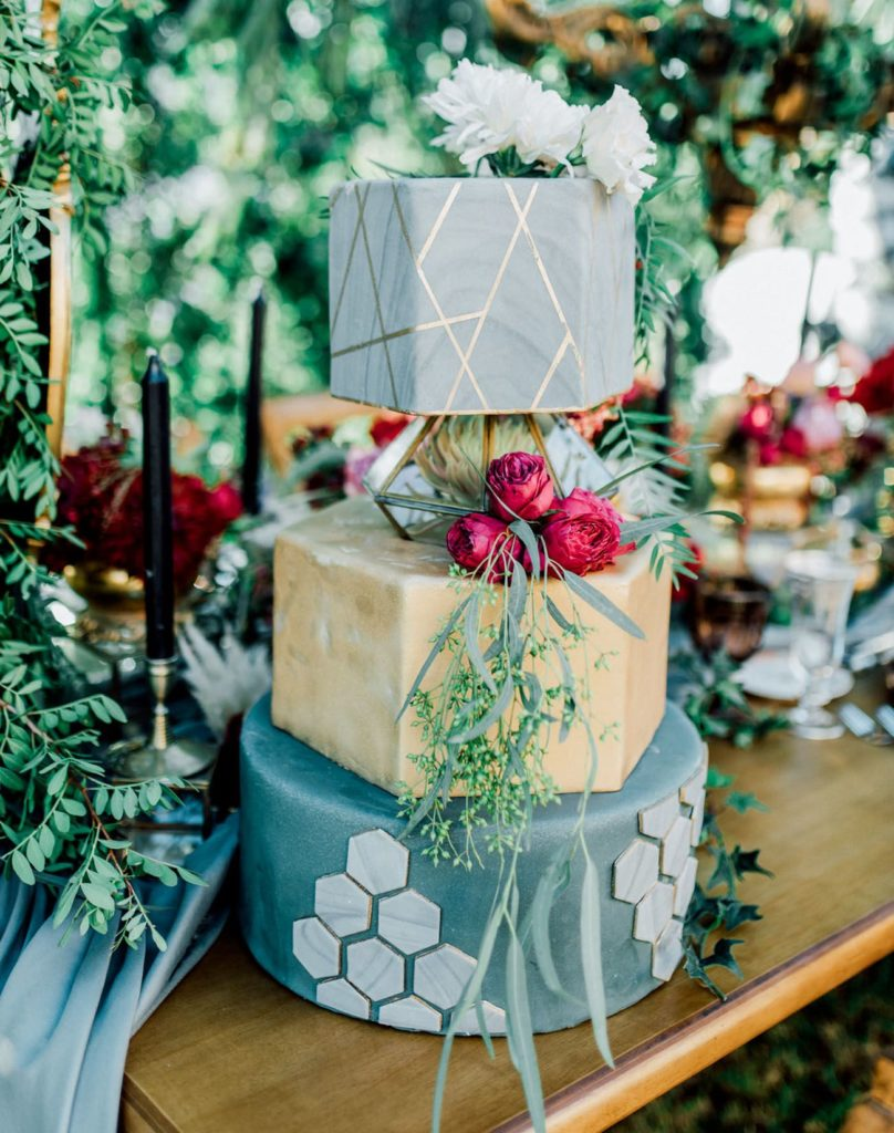Three tier wedding cake with geometric spacer between top and middle layers. Bottom layer is green with grey hexagons, middle is gold and the top layer is covered in grey fondant with gold geometric lines