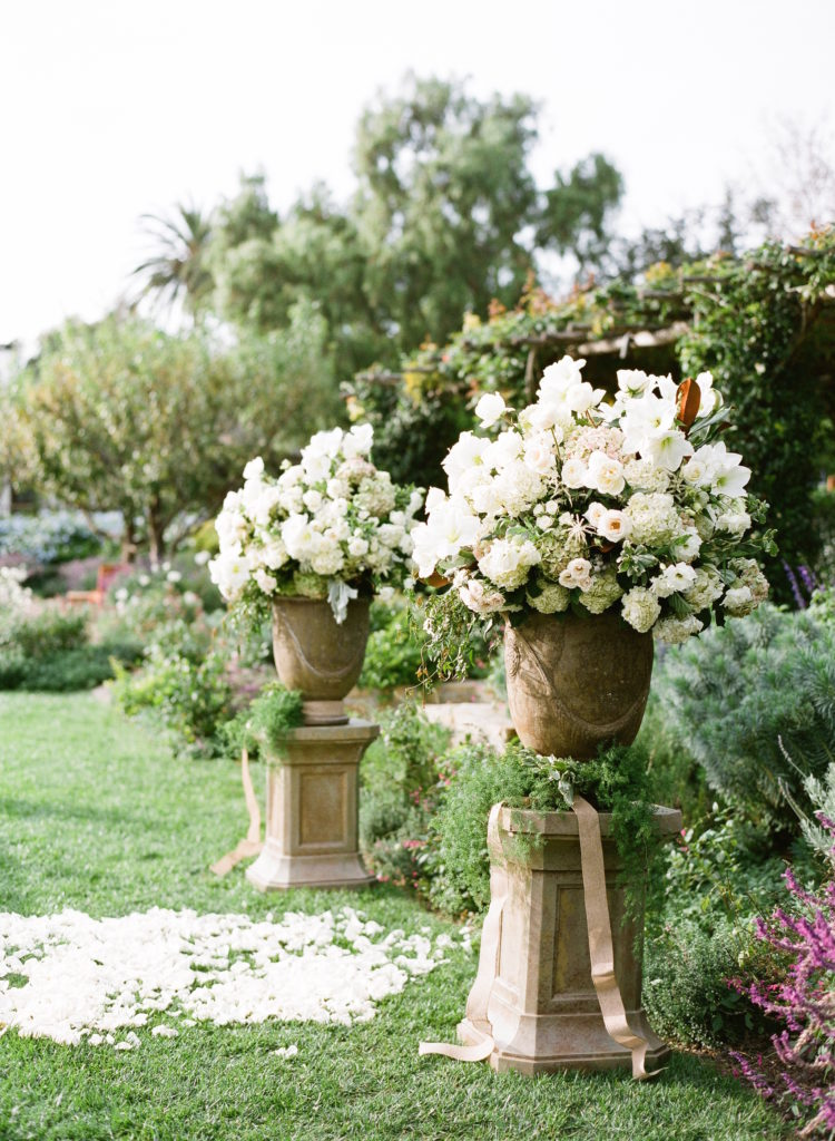 Two large stone vases full of large white flowers and greenery. At the base of the vases are beige ribbon and wrapped vines