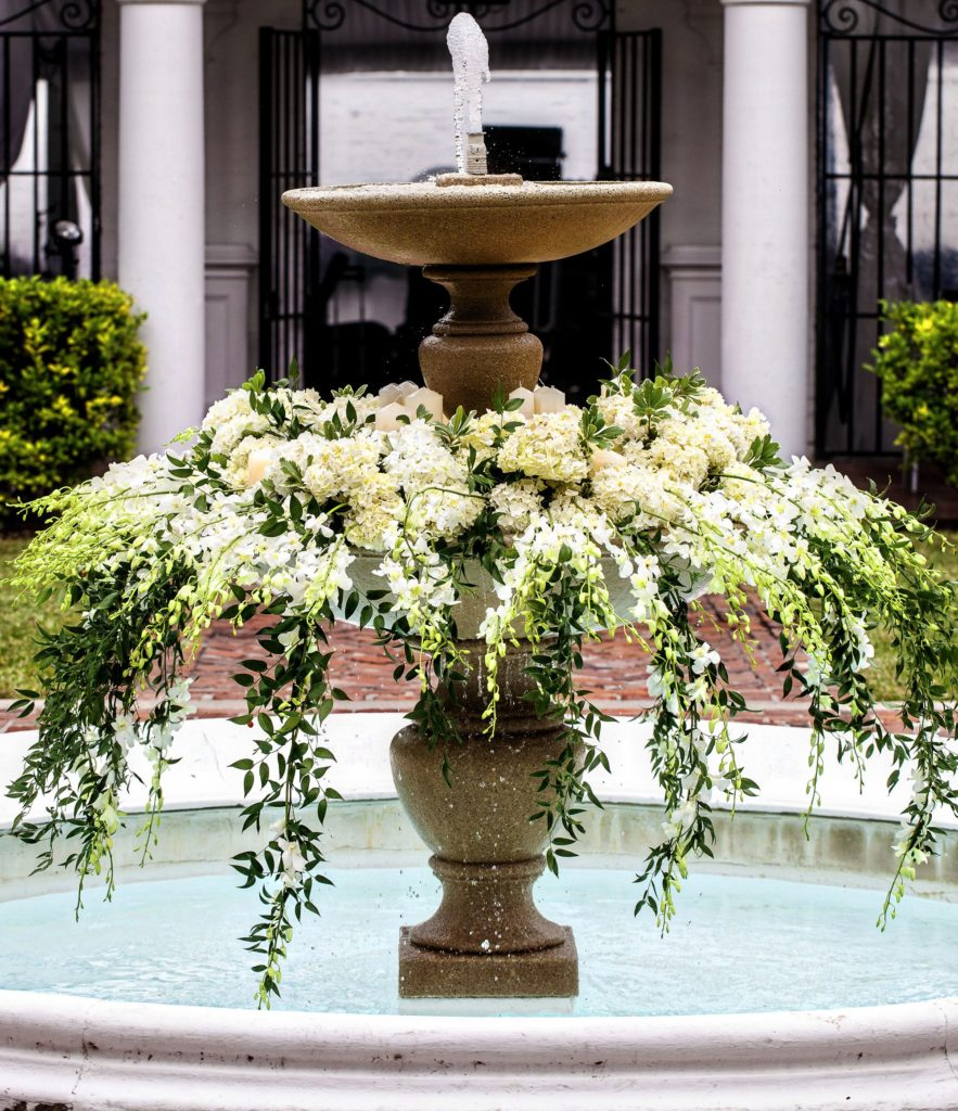 Gold, two tier fountain filled with white flowers and hanging greenery and water
