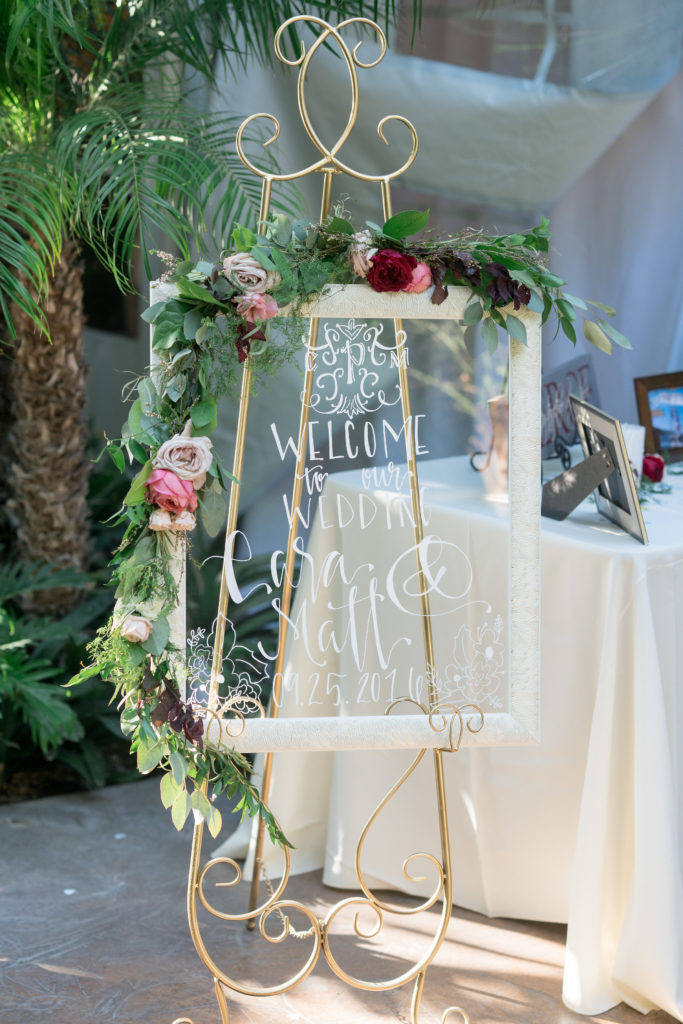"Glass pane in cream coloured frame with white calligraphy on it reading ""Welcome to our wedding, Lisa & Matt"" The frame sits on a gold stand and is decorated with a garland of greenery and pink, white and red flowers across the top, left hand side and half of the bottom"