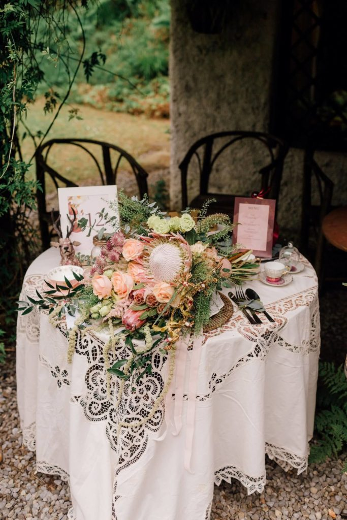 Large tied bouquet of assorted eucalyptus and grasses interspersed with pink roses and small white flowers on a small table covered in a lace white table cloth