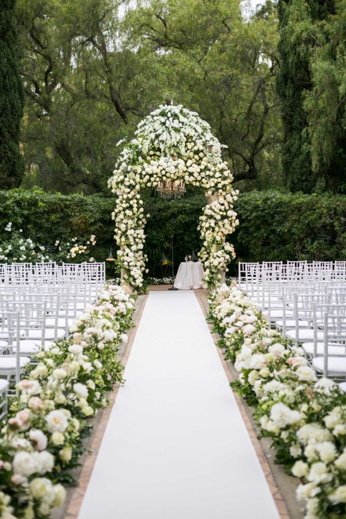 Large arch of white roses and greenery at the head of a white linen aisle bordered by white roses and greenery and white chairs