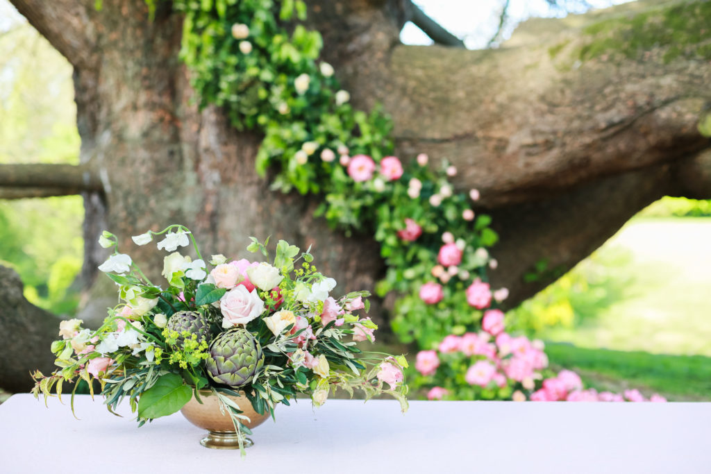 Medium sized table display of pink and white flowers, succulents and greenery displayed in a shallow gold bowl on a white table cloth