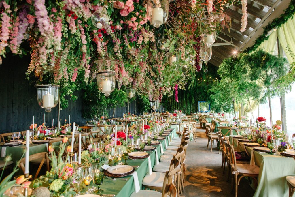 Large banquet tables with pink and green floral displays in the centre. A large mass of pink flowers, various greenery and lanterns hang from the ceiling above the tables